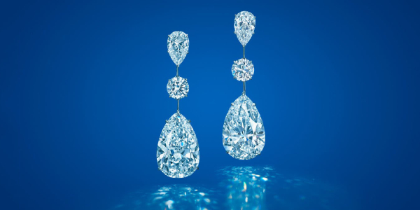 Pair of Beautiful Diamond Earrings Isolated on Blue Background.