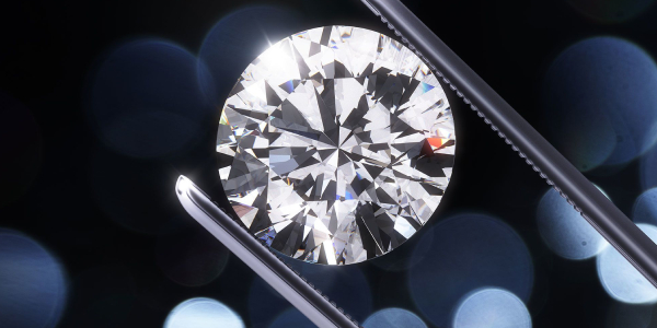 Brilliant Cut Diamond Held By Tweezers.