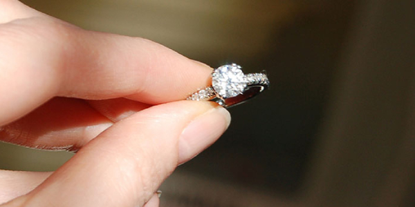 A Woman Holding A Diamond Ring On her Hand.