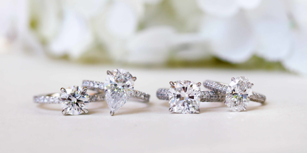 Two Pair of Diamond Rings Displayed On a White Table.